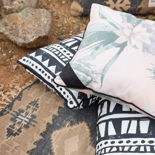 Close up of the kateen and bermuda print indoor outdoor cushions on rocky ground