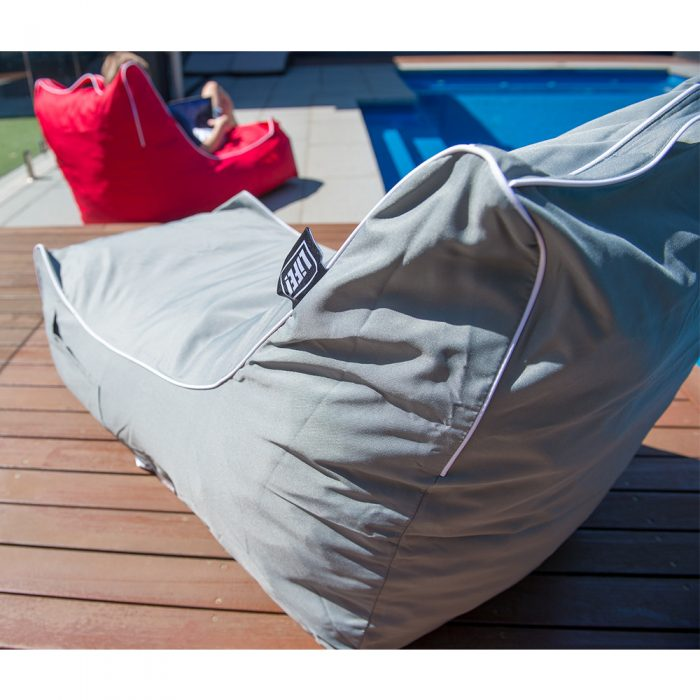 Grey coastal lounge bean bag and red coastal lounge bean back on decking beside a blue pool