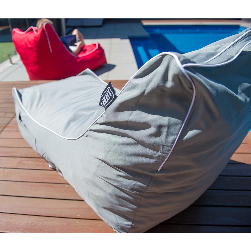 Grey coastal lounge bean bag and red coastal lounge bean back on decking beside a blue pool