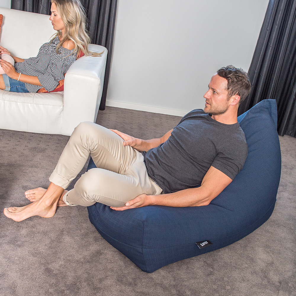 Man sits on a navy linen look luna lounge bean bag