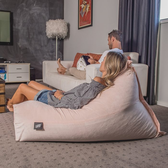 Women reclines in a pink peach velvet luna lounge shaped bean bag in a lounge room. A man sits on the couch behind using his tablet on a white gold coin print iCrib