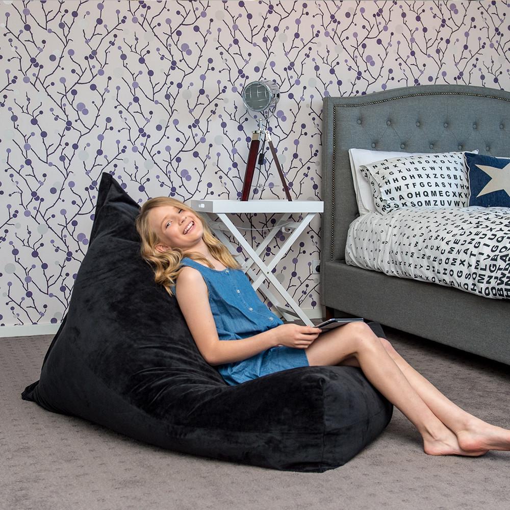 Teen reclines on a slate grey velvet luna lounge shaped bean bag in a bedroom