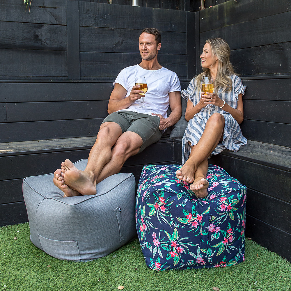 A couple relax drinking wine with their feet up on a grey linen look ottoman and blue tropical print ottoman