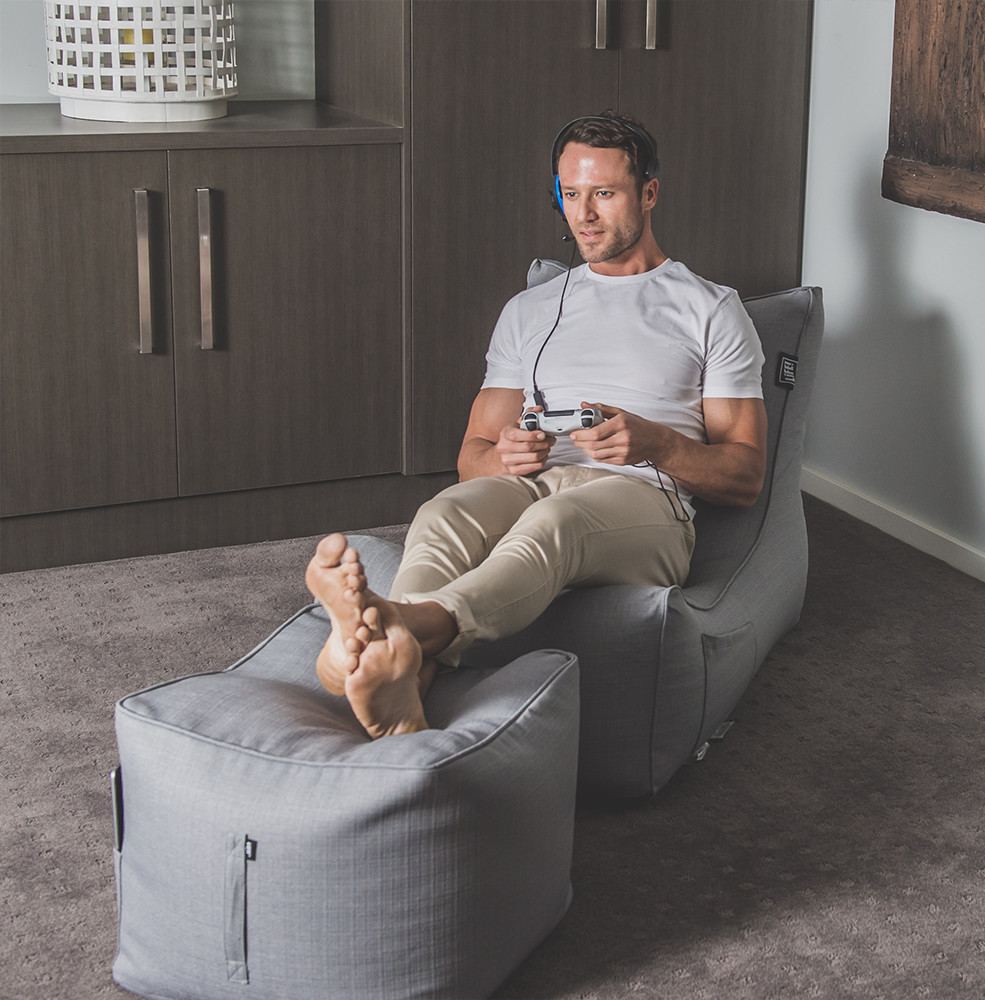 Man sits on a grey linen look coastal lounge bean bag with his feet resting on a matching grey linen look ottoman whilst holding a game console controller and wearing a headset