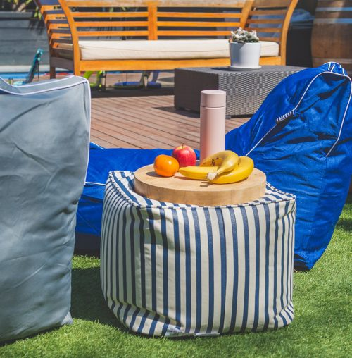 A blue and white nautical striped ottoman with a wooden cutting board upon it filled with fruit and drink bottle. It sits between a grey and a navy coastal lounge bean bag