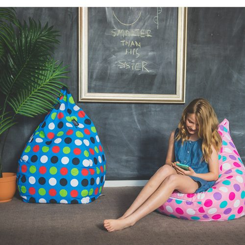 Teen sits on a vibrant pink polka dot teardrop shaped bean bag. A blue bean bag is also visible.