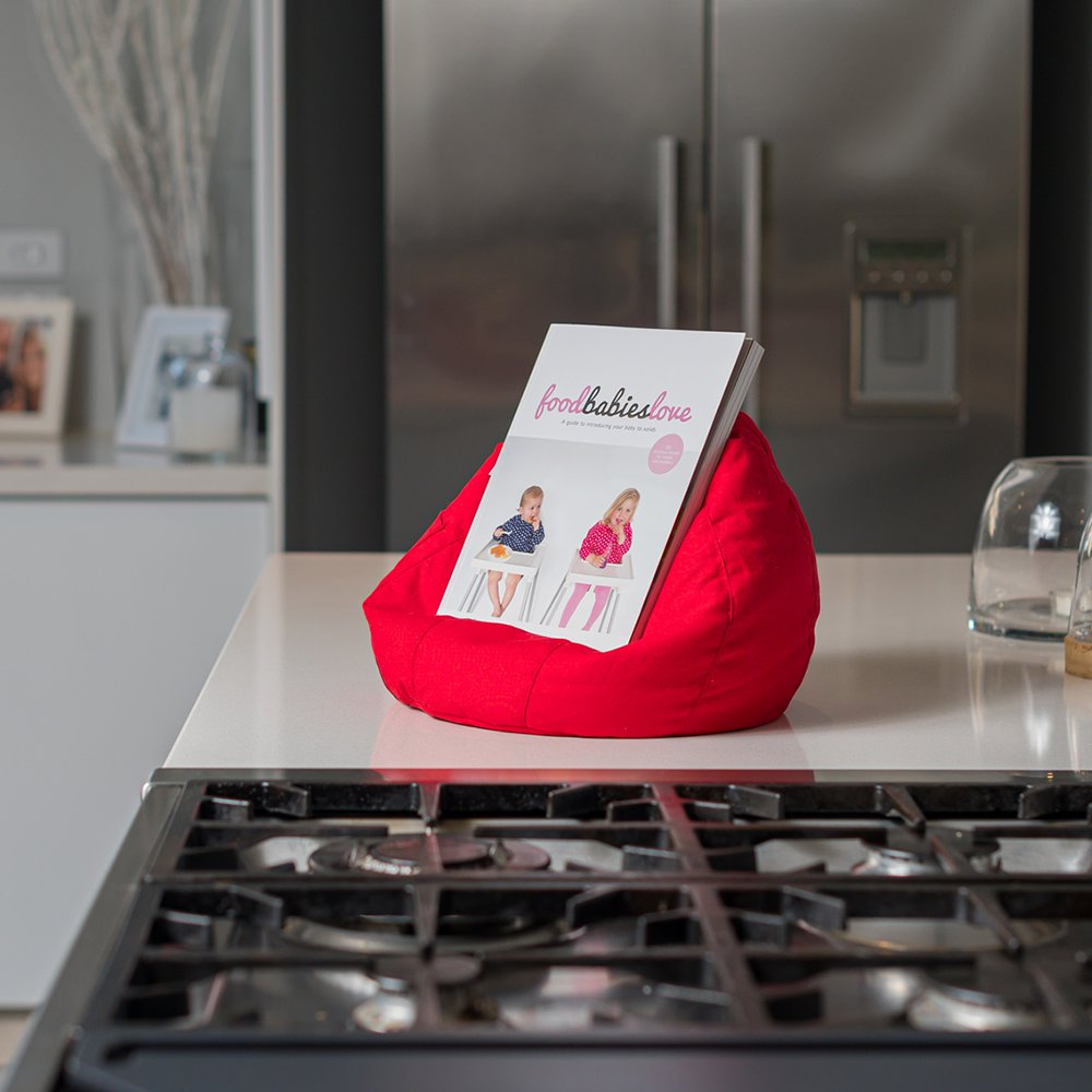 A recipe book sits in a red iCrib next to the stove