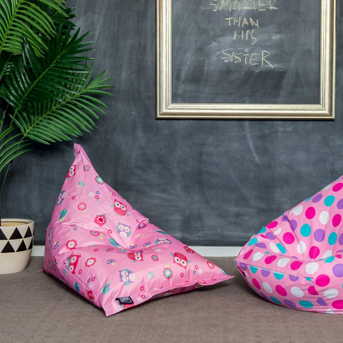 A pink sunny boy shaped bean bag is featured with a playful floral design featuring owls. A second pink beanbag with white, pink, purple and blue spots is also visible.