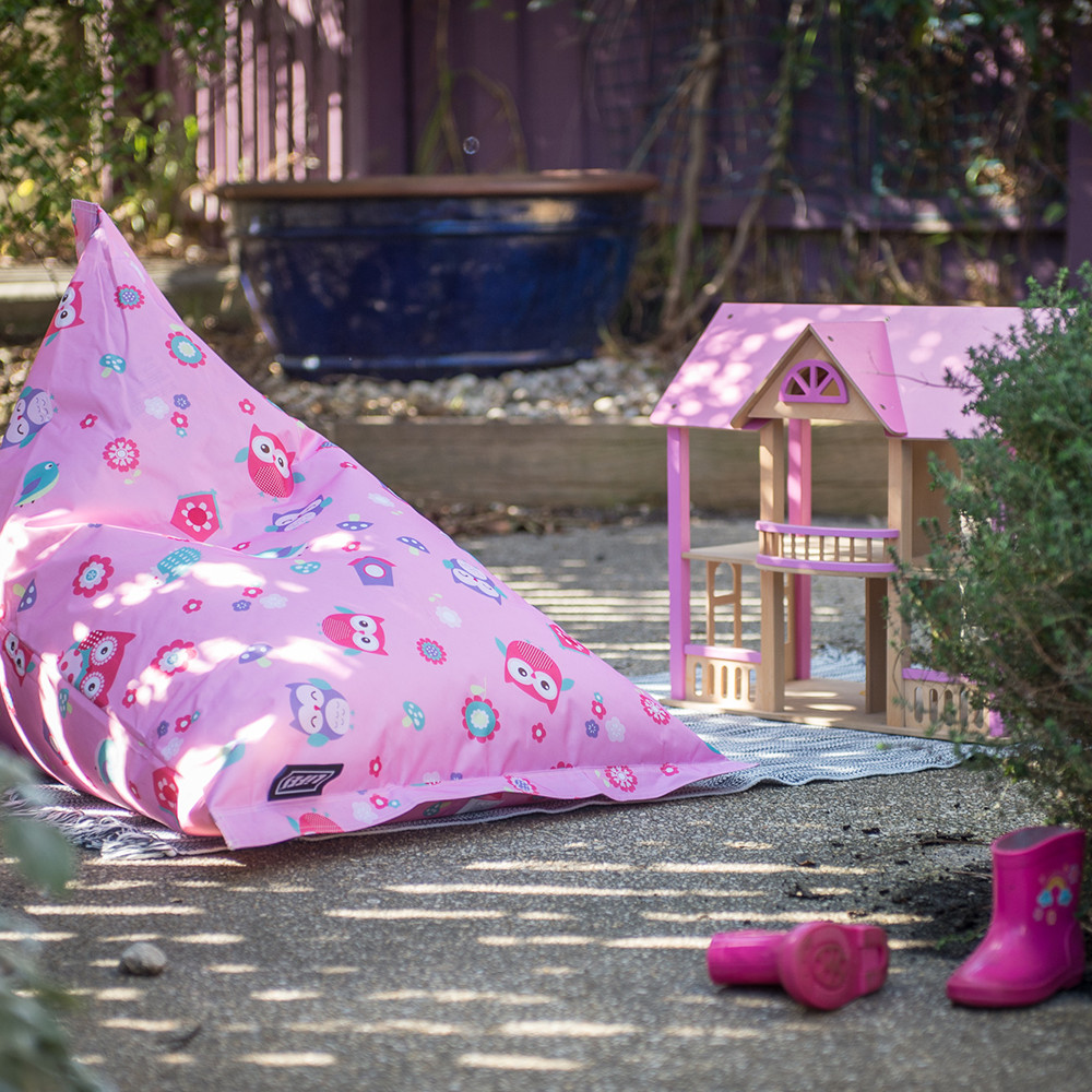 A sunny boy shaped kids bean bag sits in the garden outside next to a pink dollhouse and pink gumboots. The bean bag has a pink background with owls and flowers.