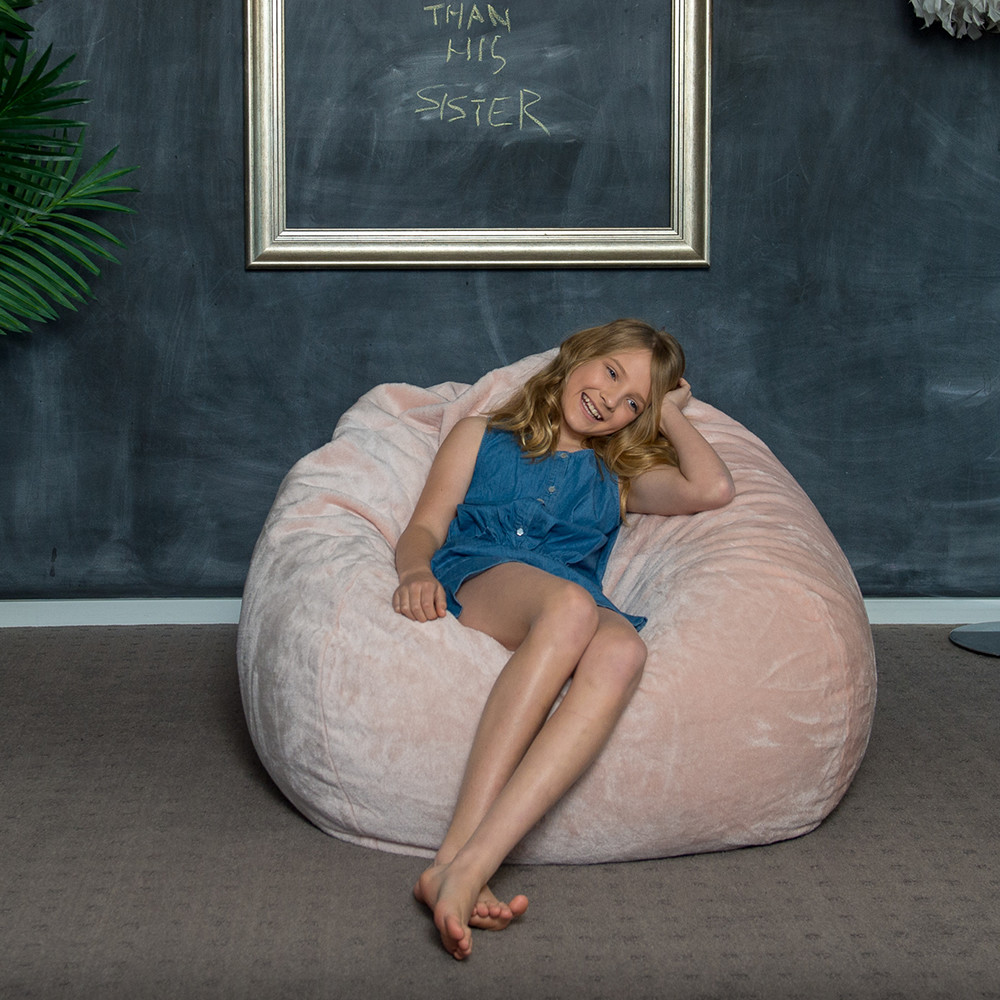 Teen reclines on the super size peach pink faux fur tear drop shaped bean bag