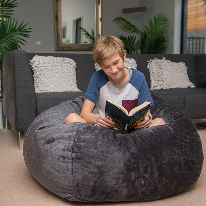 Teen sits on the super size slate grey faux fur tear drop shaped bean bag, cross legged reading a book