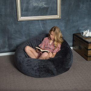Teen sits on the super size slate grey faux fur tear drop shaped bean bag, cross legged reading a book