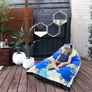 Small child reclines in the lifestyle bean bag in tier blue, yellow, green, black and white print fabric
