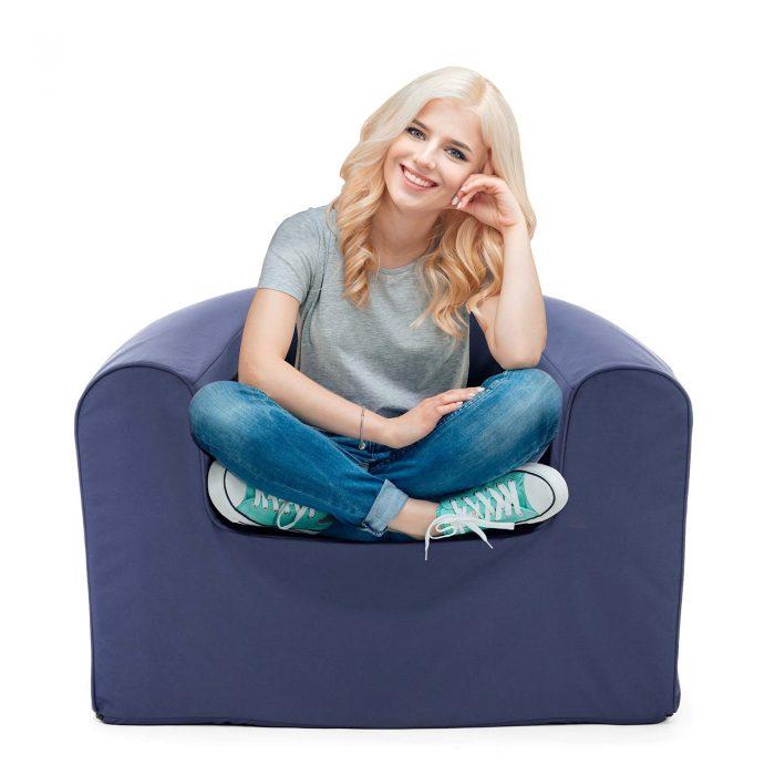 Women sits cross legged in a crown blue pop lounge foam armchair