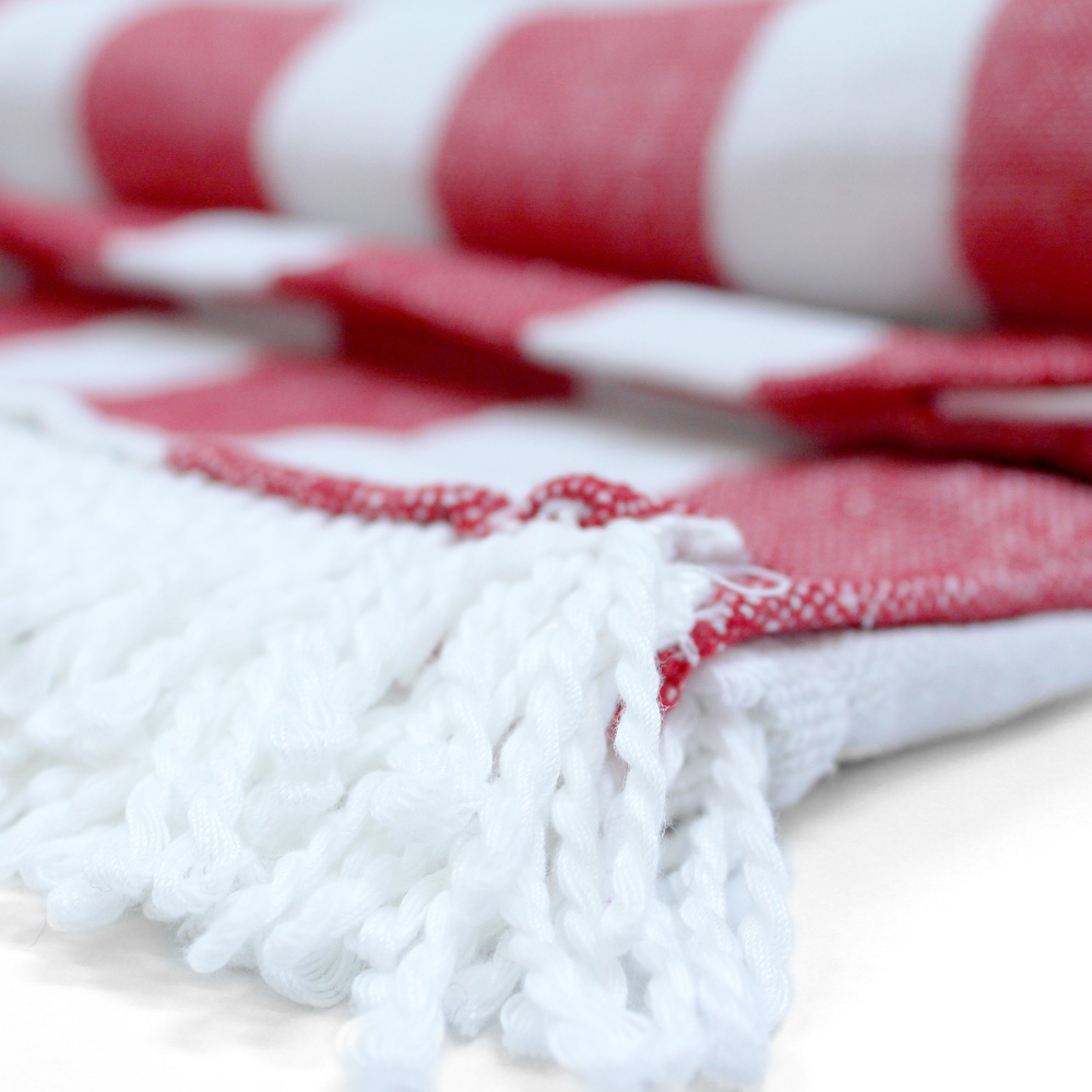 Close up of tassel fringe red and white striped beach mat picnic rug towel