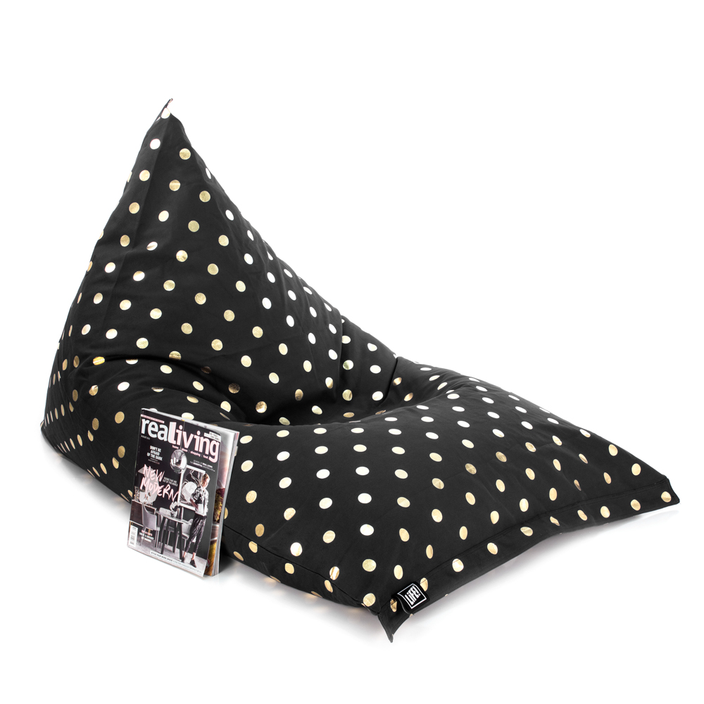 Oblique view of the black gold coin print sunnyboy shaped bean bag with a magazine resting against it
