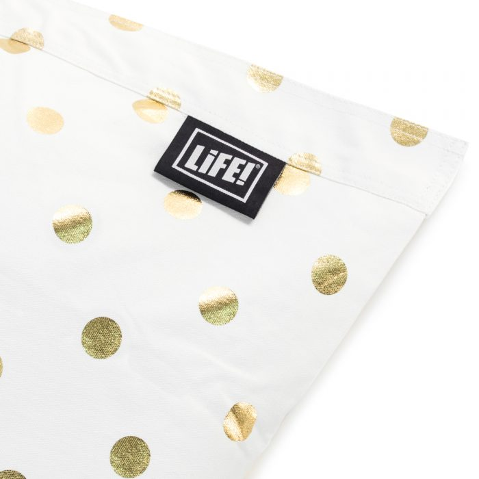 Close up of white fabric detail with gold coin spot dot print