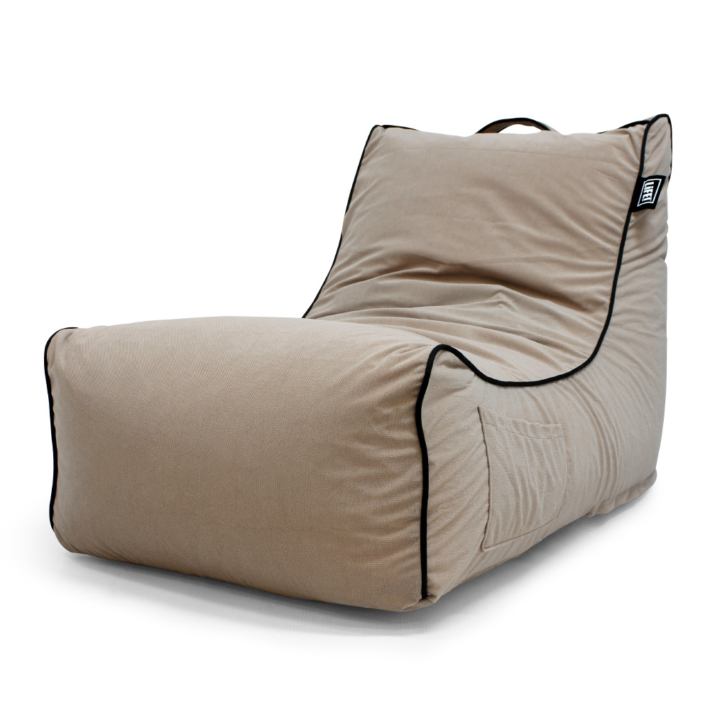 Coastal haven pop lounge in tan velour showing the storage pocket, handle and black contrast trim