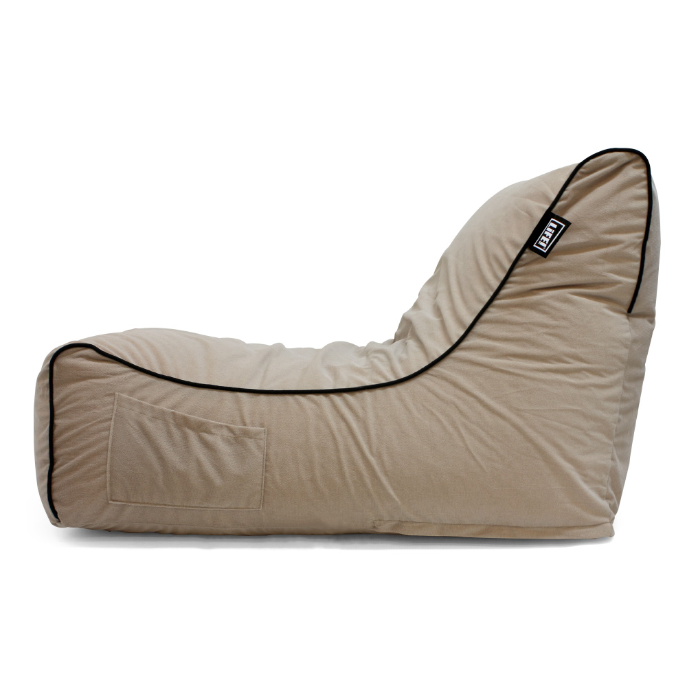 Side view of the tan velour coastal haven pop loung showing the pocket and contrast black piping