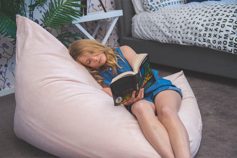 A teen snuggles into a luna pink velvet bean bag reading a book