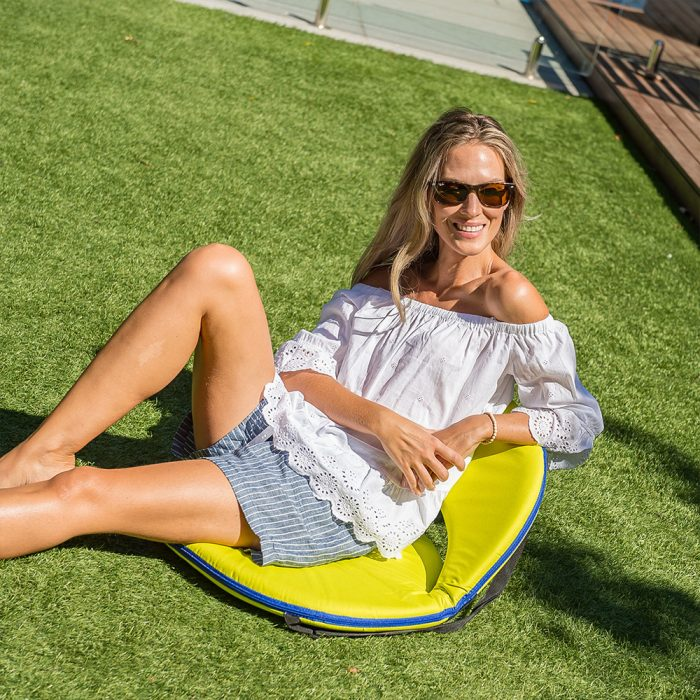 A woman soaks up the sun on the lawn seated on a beach cushion recliner chair in yellow with blue trim
