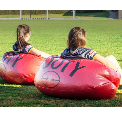 Two women sitting on large football bean bags on a grass football oval