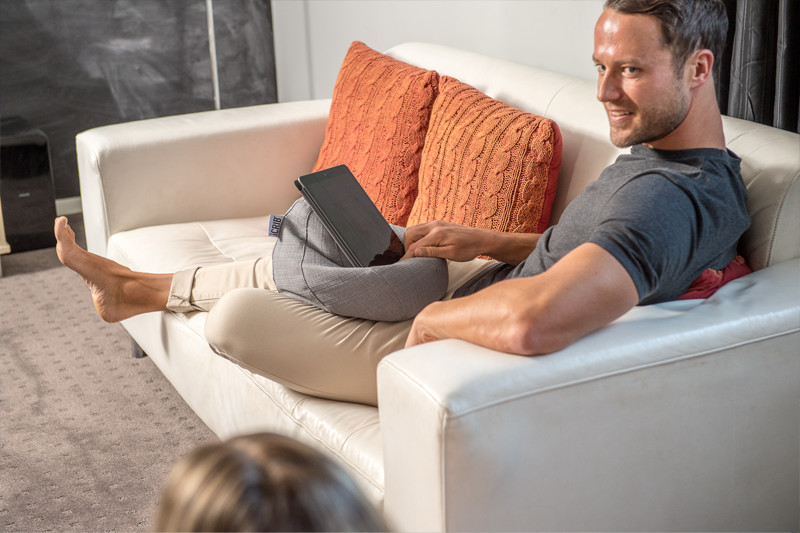 A man sits on a couch with a grey linen look iCrib on his lap holding his ipad, tablet, smart device