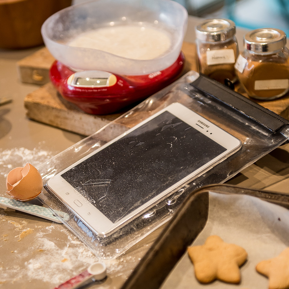 Dryz tablet protector shown with tablet inside and cooking mess around, flour, eggshells, cookies and scales