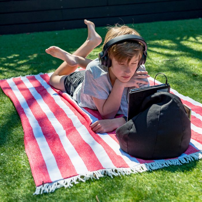 Teen laying on a red striped beach mat rug towel watching a ipad on a black iCrib