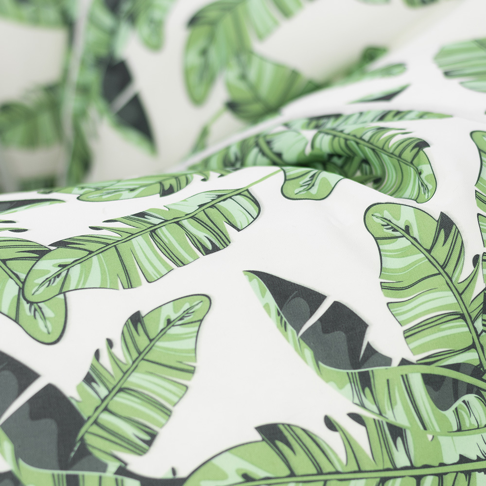 Close up of the tiki print with green montserrat palm leaves on a white background