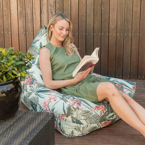 a woman reads a book sitting on a waikiki print luna bean bag on a deck outdoors
