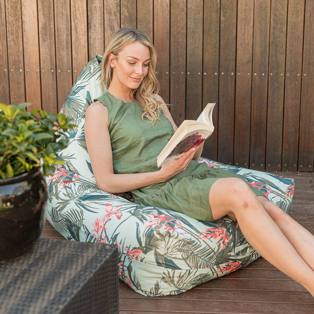 a woman reads a book sitting on a waikiki print luna bean bag on a deck outdoors