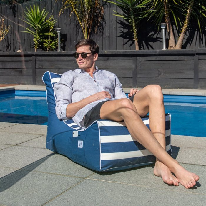 A man recliners in a navy nautical stripe coastal lounger bean bag by the pool