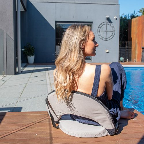 A woman sits poolside on a grey ozark cushion recliner portable chair