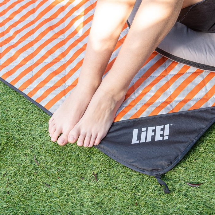 A teens feet sit on the edge of a retro striped picnic blanket with the LiFE! logo visible on the privacy pocket