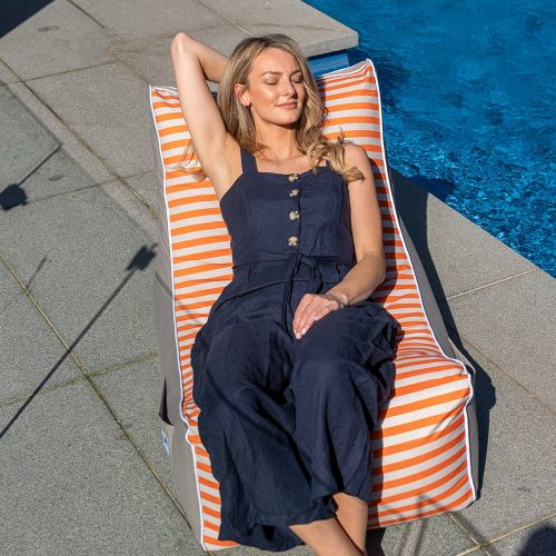 A woman reclines on a retro stripe coastal lounger bean bag by the pool