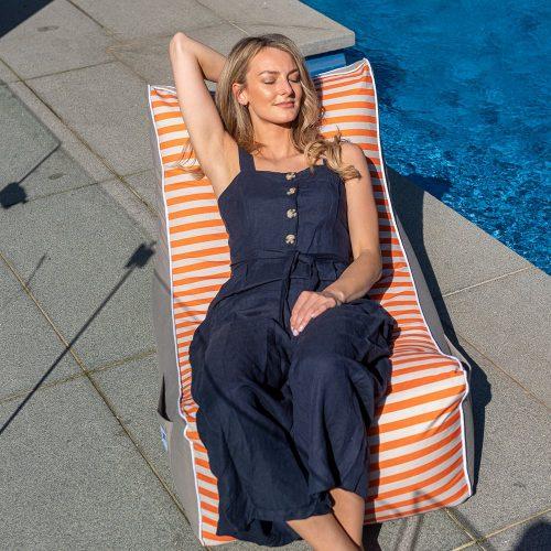 A woman reclines on a retro stripe coastal lounger bean bag by the pool