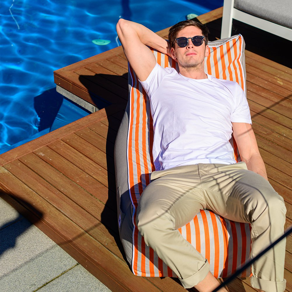 A man reclines on a retro stripe coastal lounger bean bag by the pool