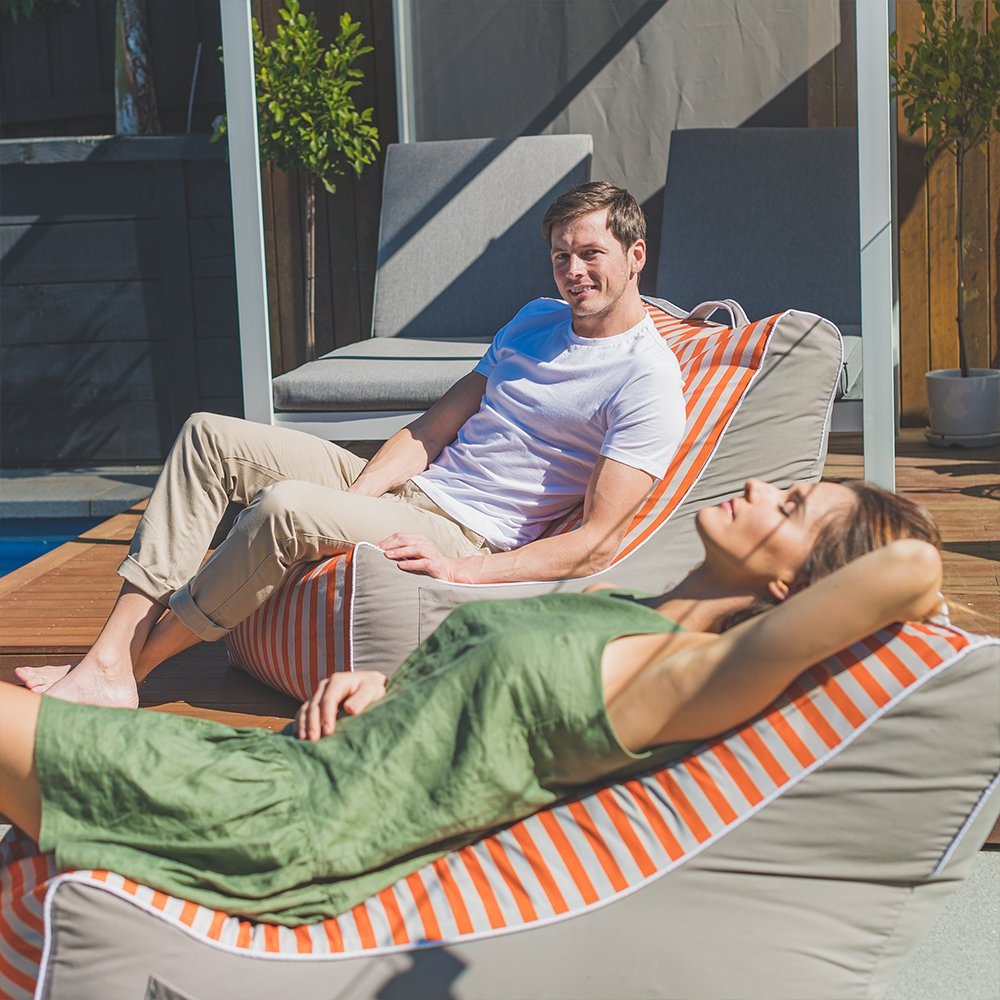 A couple recline in the sun on retro coastal lounger bean bags