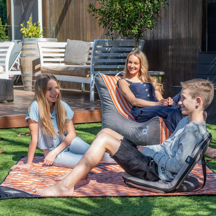 A family sit on a series of coordinated products - the retro stripe coastal lounger, matching adventure mat and grey cushion recliner