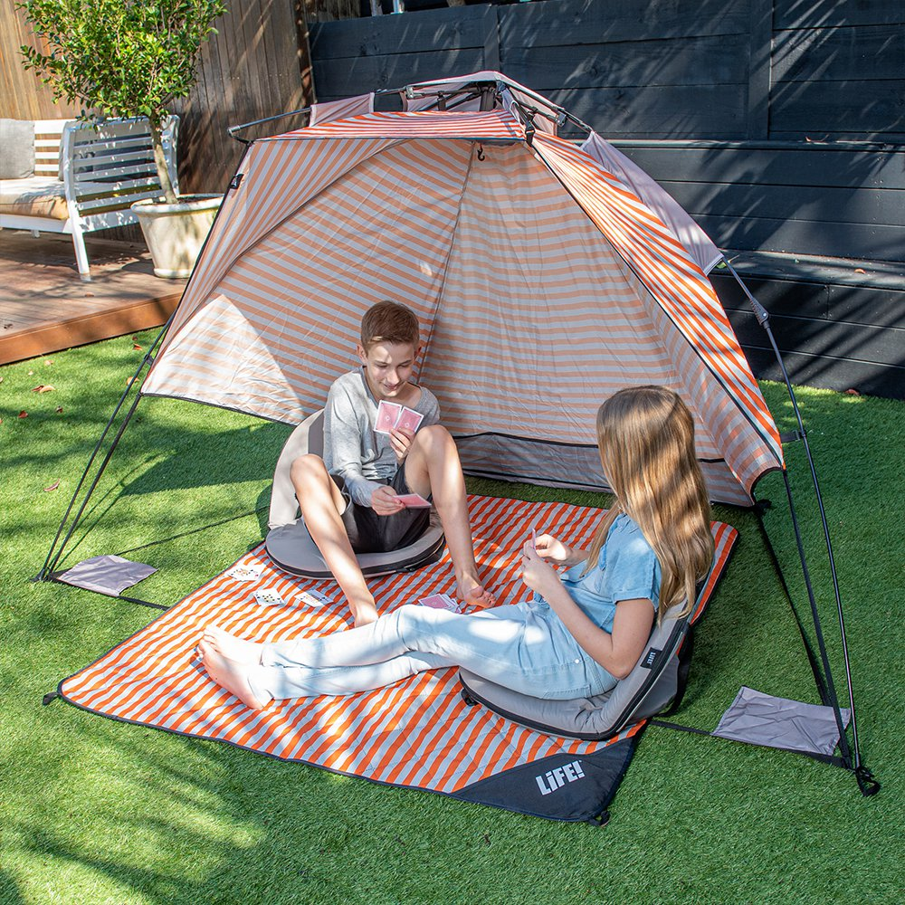 Two tweens play cards on a retro stripe picnic rug under a retro stripe easy setup sun shelter