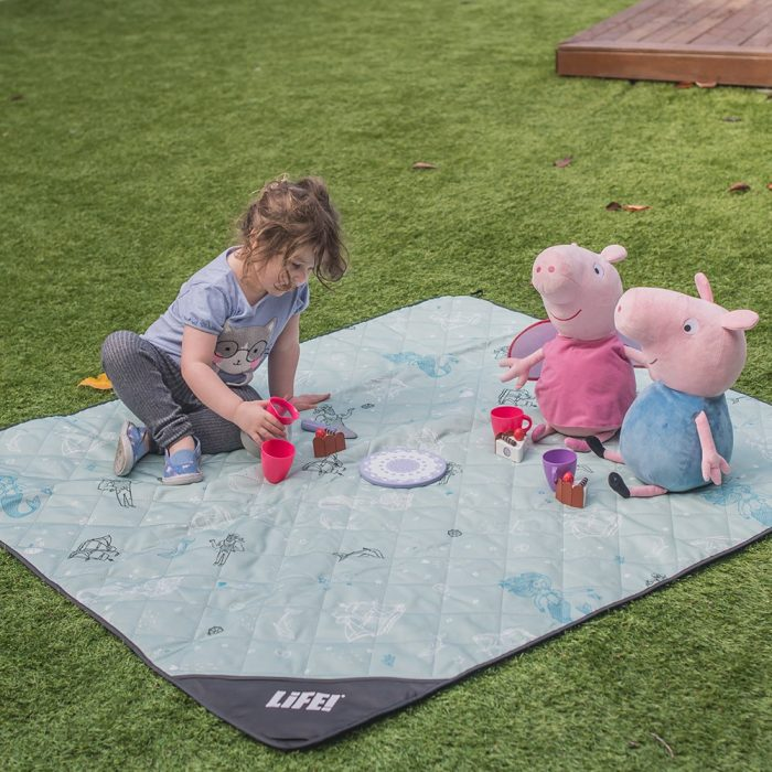 A toddler picnics with toy pigs on a teal green adventure mat picnic rug. The sea of love print features mermaids, sailors, boats and dolphins