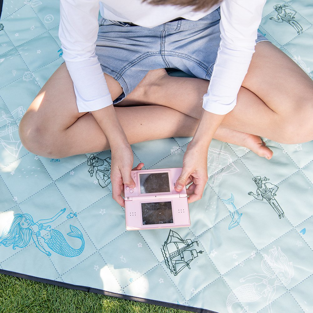 A teen holds a gaming console above the sea of love adventure mat picnic rug