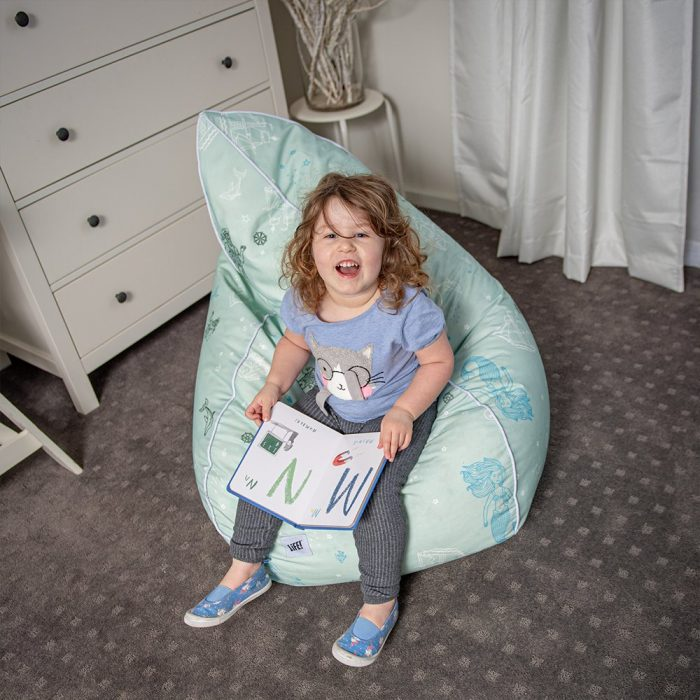 A toddler sits on a sea of love print bean bag featuring mermaids, sailors and dolphins
