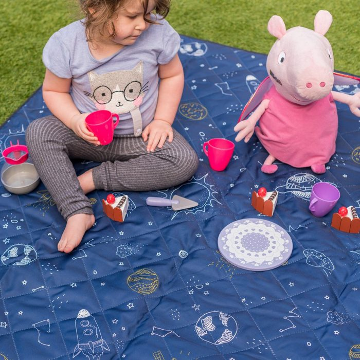 A toddler shares a tea party with peppa pig toy on a space buddy print adventure mat picnic blanket