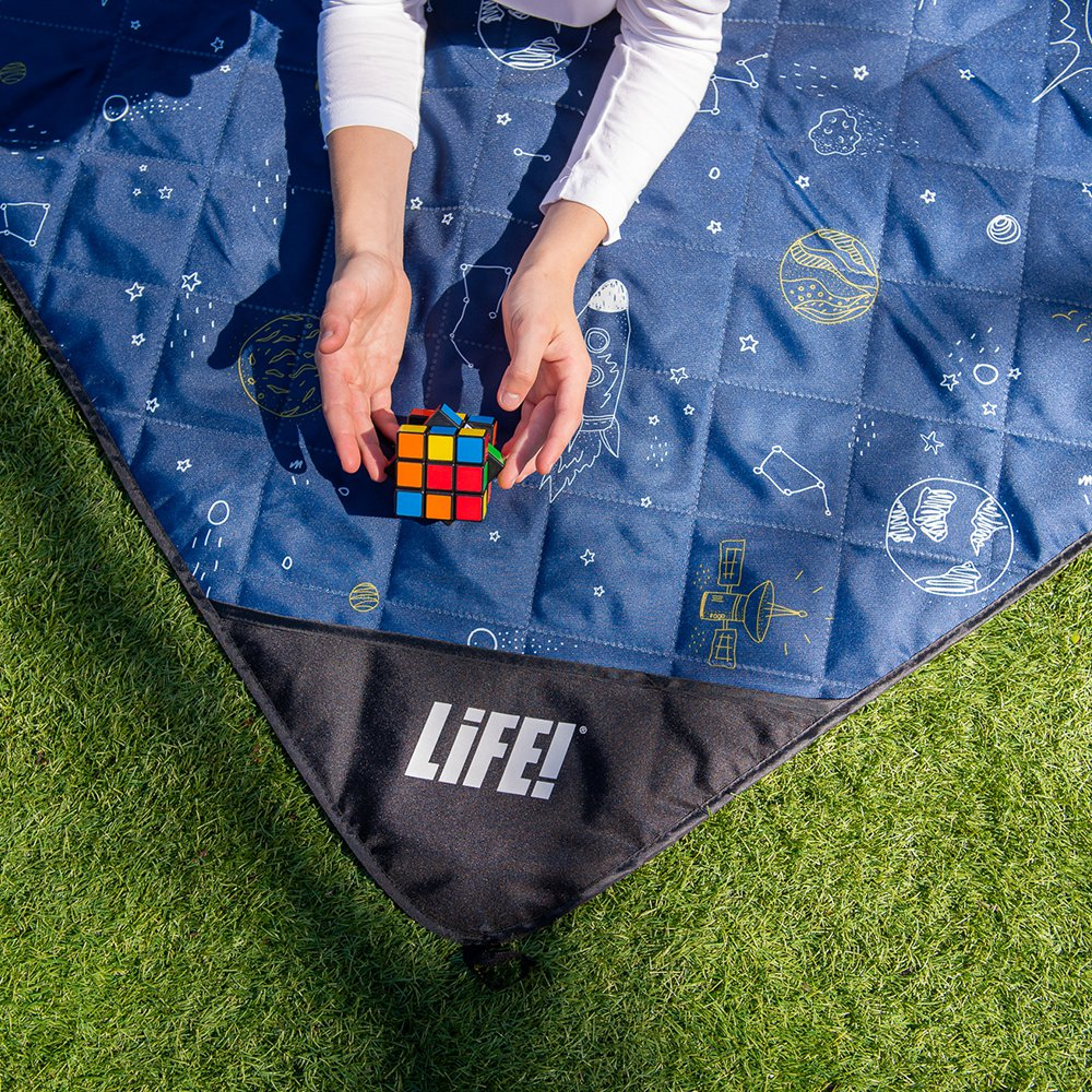 A teen plays with a rubics cube on a blue space buddy picnic rug. It has planets, stars and rockets printed in white