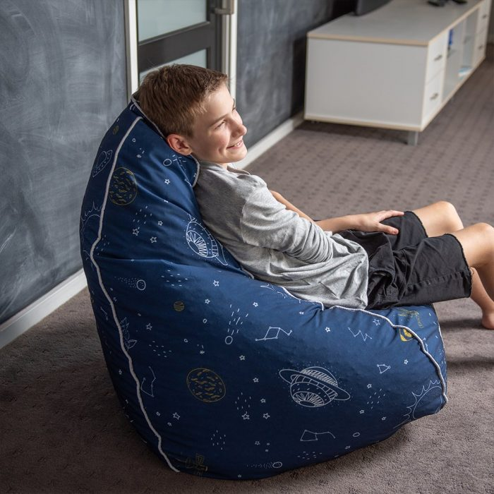 A teen sits in a blue space buddy print bean bag. The outer space print featuring planets and stars is white like the contrast piping trim