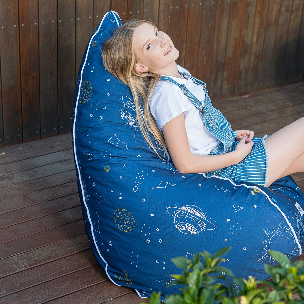 A teen reclines on a space buddy teardrop bean bag. It is blue with a white outer space themed print