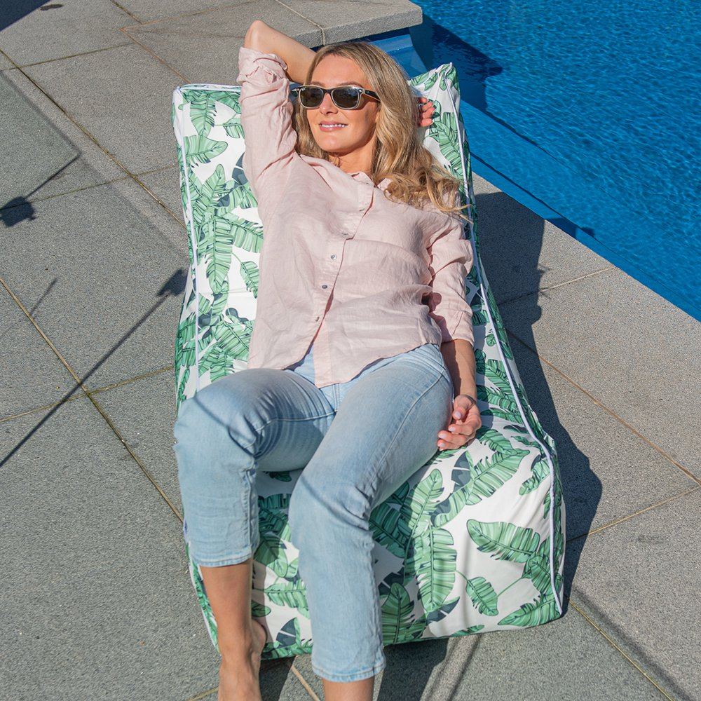 A woman reclines in the sunshine relaxed in a leaf tiki print coastal lounger bean bag by the pool
