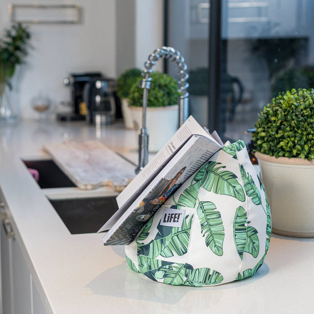 A recipe books sits on a tiki print iCrib on a kitchen bench